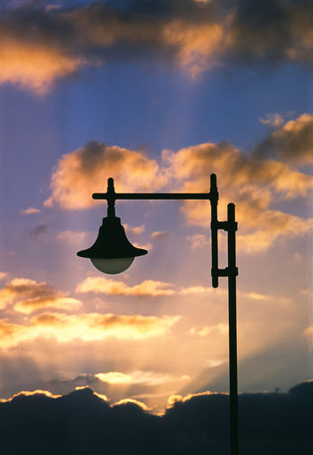 Low angle view of silhouette street light against orange sky