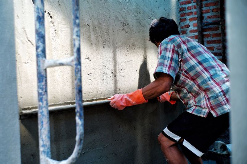 Worker plastering the cement texture on the brickwork wall with the shadow at construction site
