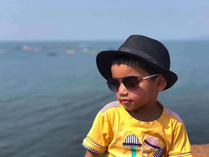 Boy wearing sunglasses and hat against sea