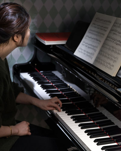 Practicing at the Grand Piano Asian Woman Dark Hair Arts Culture And Entertainment Classical Music Close-up Day Human Hand Indoors  Keyboard Instrument Learning Music Musical Instrument Musical Note Musician One Person People Pianist Piano Piano Key Playing Practicing Real People Sheet Music Skill  Young Woman Playing