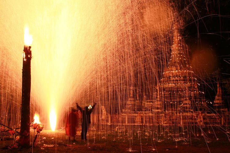 People Celebrating With Fireworks At Temple During Night