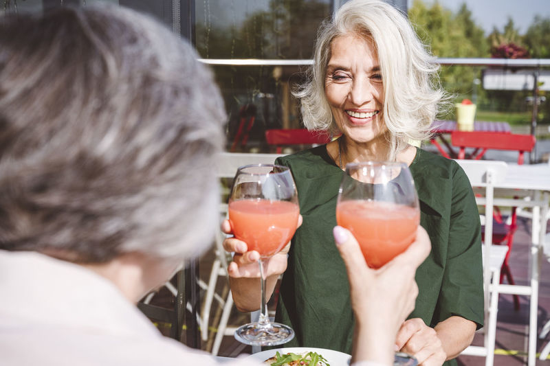 Portrait of smiling woman with drink on table