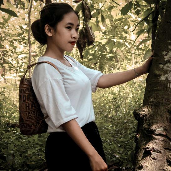 Teenage girl looking away while standing against tree trunk