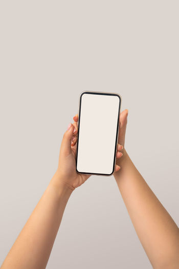 Low section of person holding smart phone against white background