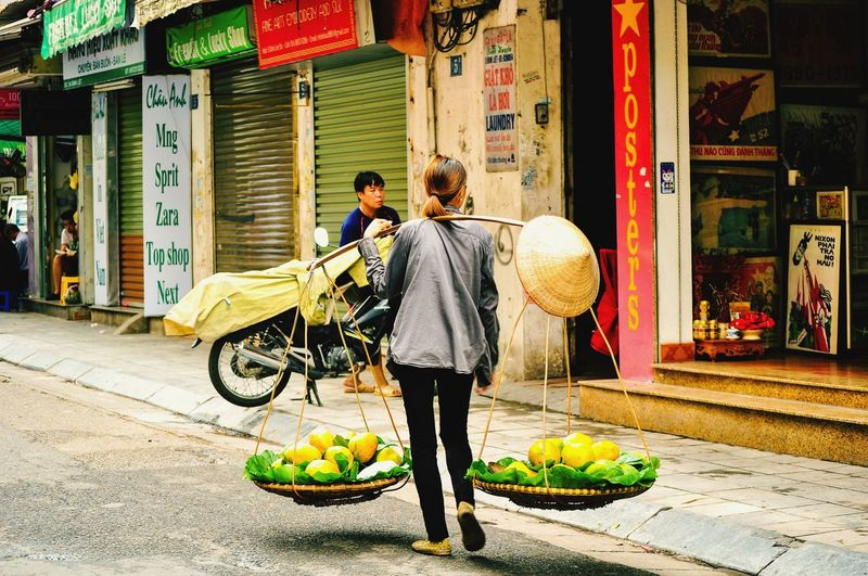 Rear View Of Female Vendor Selling Fruits On Street In City