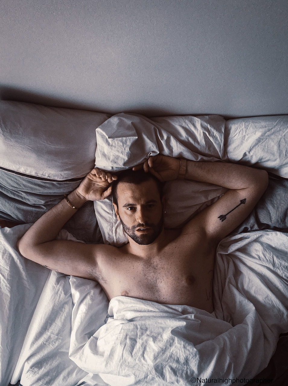 HIGH ANGLE PORTRAIT OF YOUNG MAN LYING ON BED