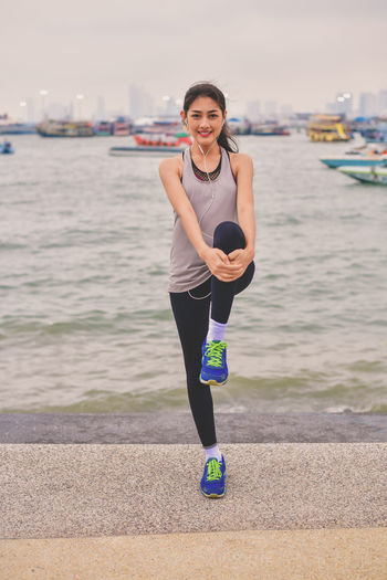 Happy young woman exercising on promenade at beach in city