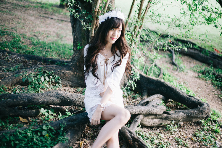 Beauty in White Dress One Person Young Adult Leisure Activity Real People Casual Clothing Hairstyle Hair Beautiful Woman Outdoors Contemplation Tree Plant Sitting Portrait Nature Front View Day Land Tree Trunk Looking At Camera Three Quarter Length Trunk Fashion