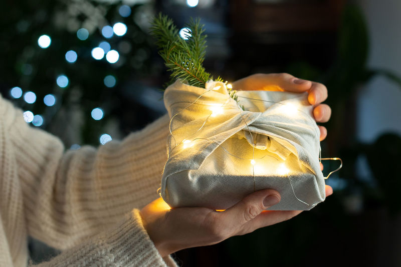 Cropped hands of woman holding illuminated christmas decoration