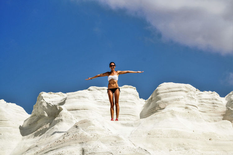 Low angle view of young woman wearing bikini while standing on rock formation against sky during sunny day