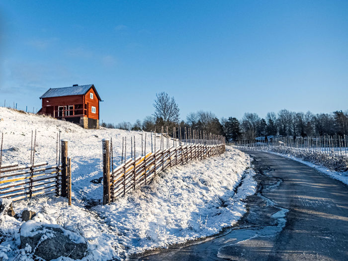 Snow covered houses by building against clear sky during winter