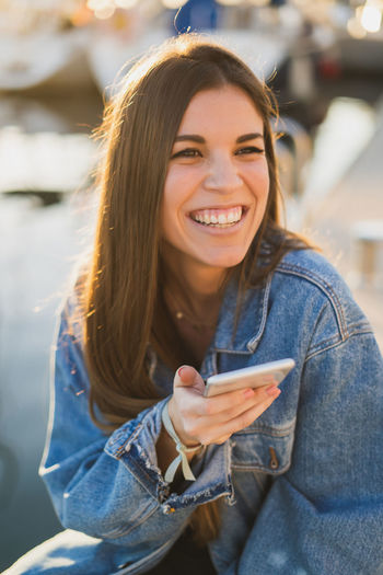 Cheerful woman using phone while sitting outdoors
