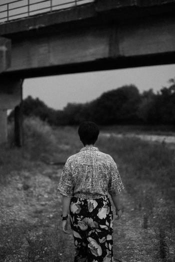 Rear view of a woman walking on under a bridge