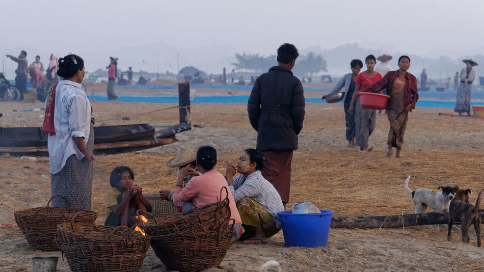 Sitting in front of a fires place warming up for things to come Fishing Village Market Rakhine State Adult Basket Beach Day Domestic Animals Field Lifestyles Mammal Medium Group Of People Men Myanmar Nature Outdoors People Pets Real People Sky Warm Clothing Women