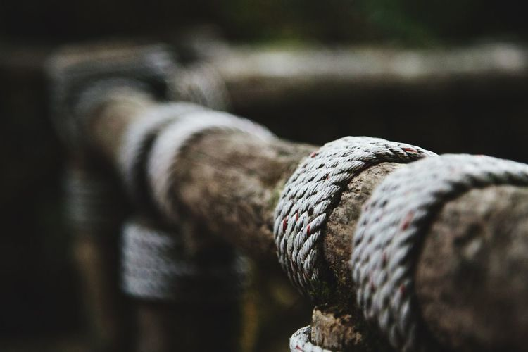Close-Up Of Rope Rolled On Wooden Railing