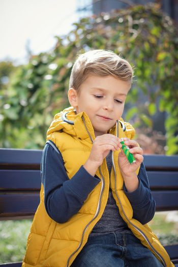 Boy holding candy while sitting on bench at park