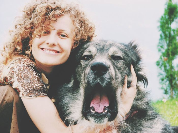 Portrait Of Happy Young Woman Embracing Caucasian Shepherd Dog