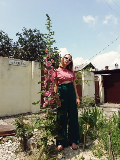 Young woman standing by plants against sky
