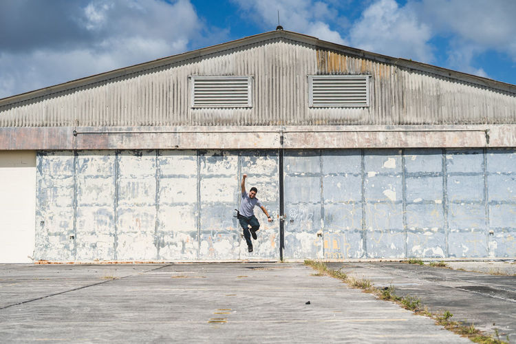 Full length of man jumping over pathway against old building