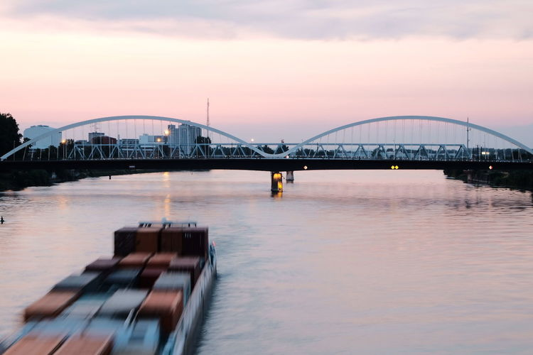 Bridge Over River In City Against Sky At Sunset