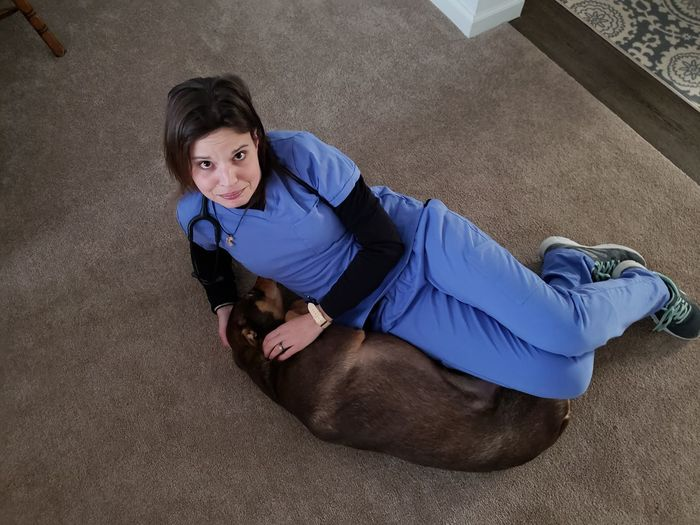 High Angle Portrait Of Woman Lying With Dog On Floor