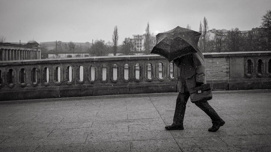 Side view of woman with umbrella walking against built structure