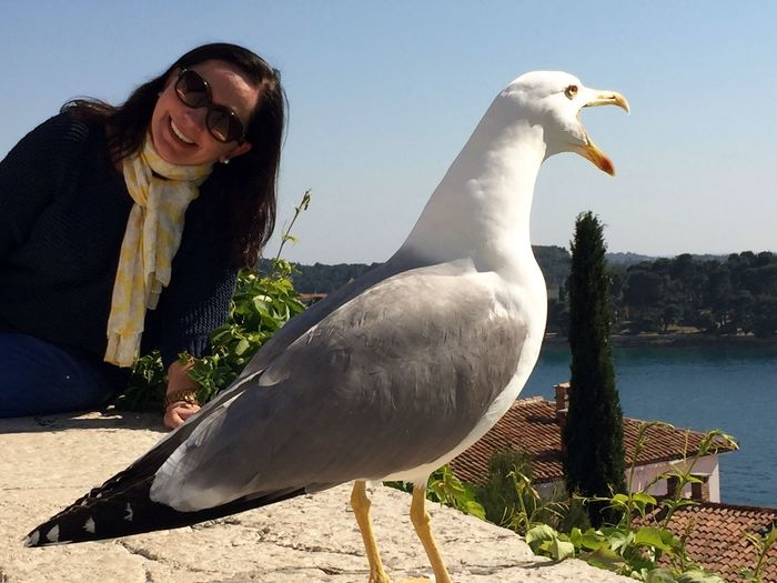 Portrait Of Smiling Woman By Seagull At Lakeshore Against Clear Sky