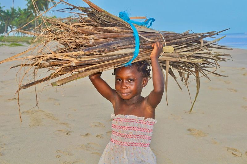 Portrait of girl carrying logs on beach