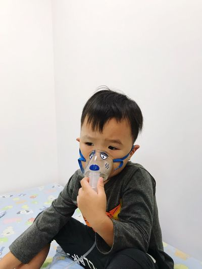 Boy With Oxygen Mask Sitting On Bed At Home