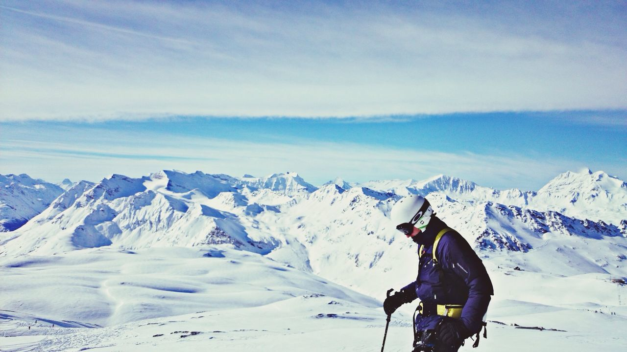 Side view of skier on snowcapped landscape