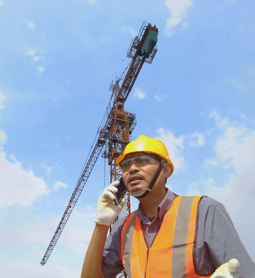 Low angle view of man holding crane against sky