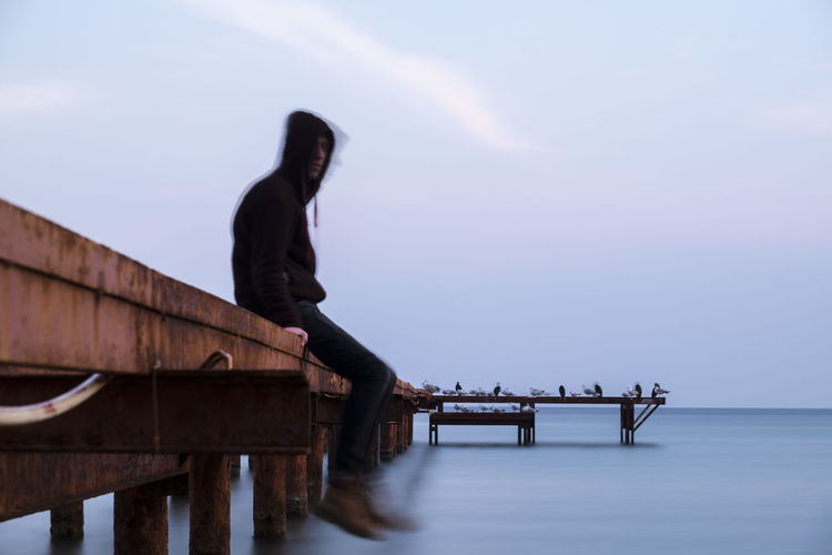 Side view of man sitting on pier over sea during winter