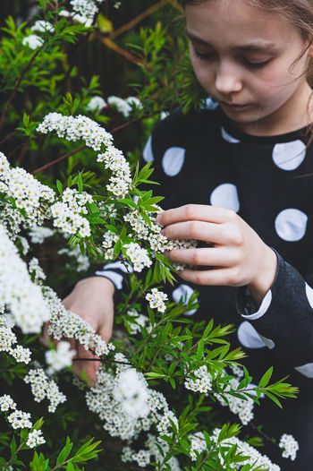 Cute girl touching flowering plants