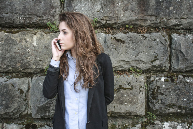 Businesswoman talking on mobile phone while standing by weathered stone wall
