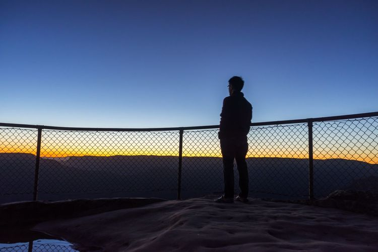 Silhouette Man Standing At Observation Point Against Clear Blue Sky At Morning