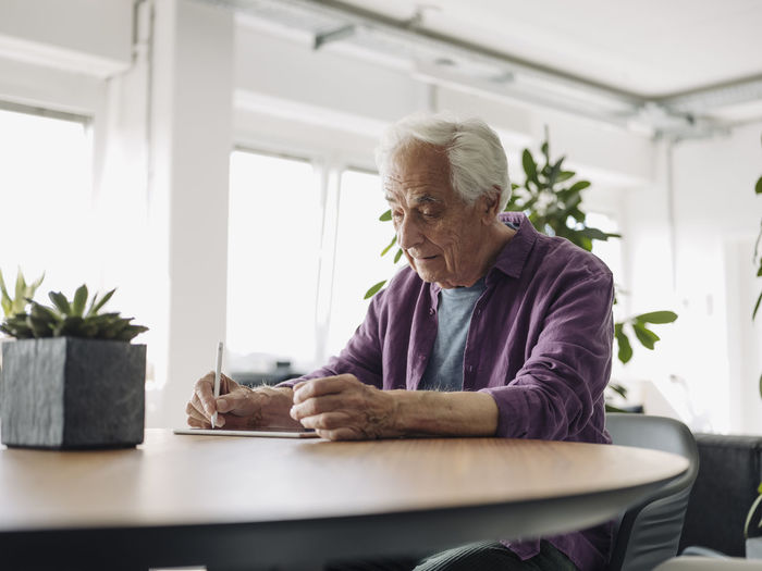 Man looking away while sitting on table