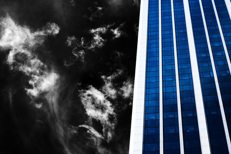 Part of a modern building with blue windows beside dark sky with white clouds. Cityscape Dark Architecture Blue Building Exterior Built Structure Glass Growth Low Angle View Modern Mysterious No People Patterns Selective Color Sky Skyscraper Straight Lines Universe Windows