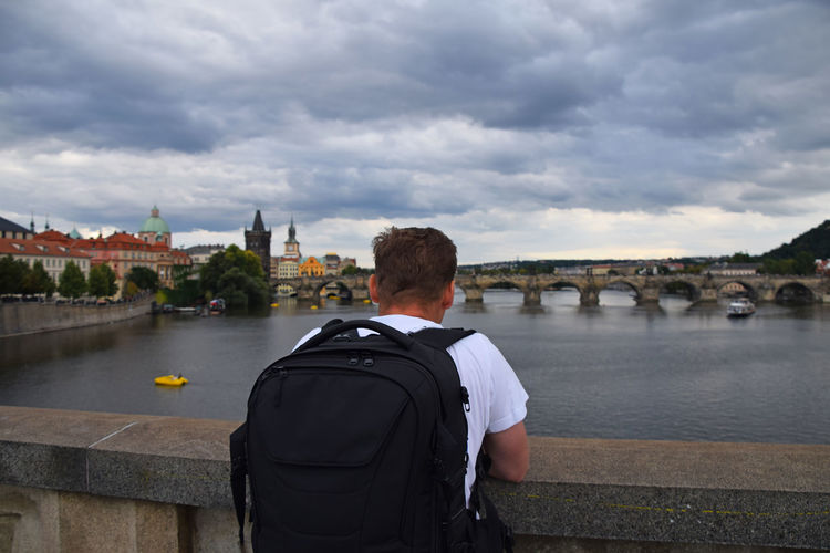 Rear view of man with backpack looking at charles bridge