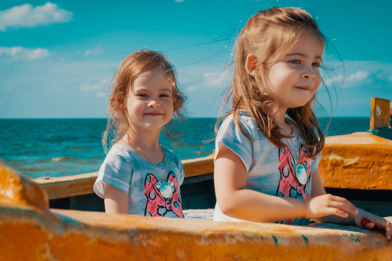 Summer Child Girl Kid Sea Beach Water Sky Boat Fisherman Boat Twins Sisters Sister Childhood Girls Females Women Real People Togetherness Innocence Cute Family Front View Lifestyles Leisure Activity Portrait Emotion Two People