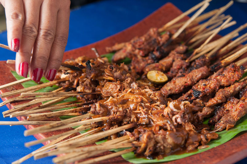 Midsection of person on satay or barbecue grill
