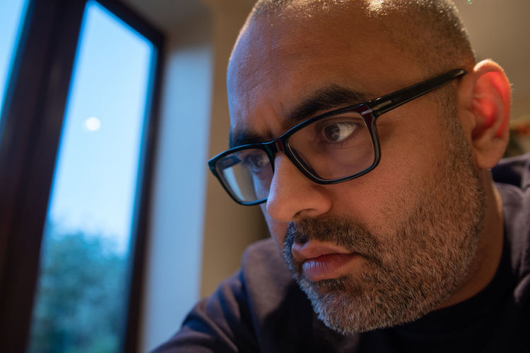 Close-up of man wearing eyeglasses at home