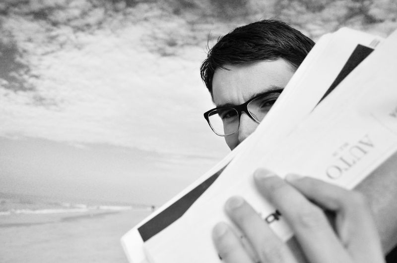 Adult Beach Boy With Glasses Close-up Cloudy Glasses Holding Lifestyles Man With Glasses Newspaper One Person Outdoors People Real People Sky Water Young Adult Blackandwhite EyeEm Black&white! Black And White Uniqueness Long Goodbye The Street Photographer - 2017 EyeEm Awards Black And White Friday This Is Masculinity