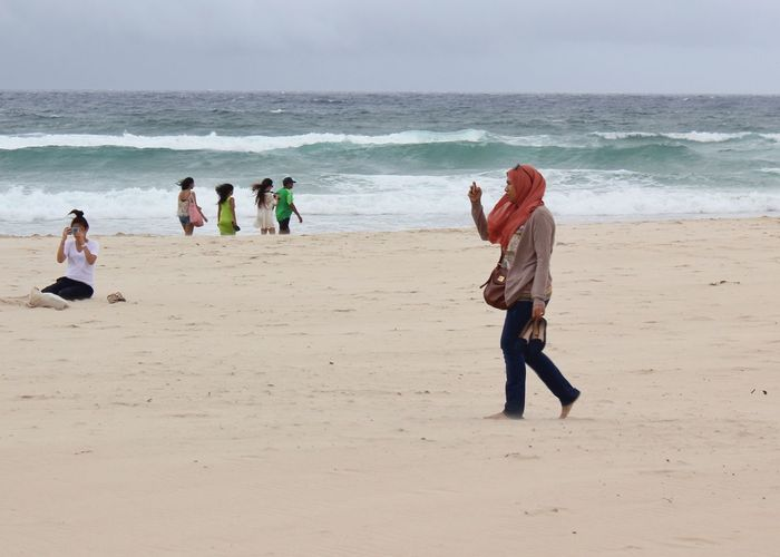 Muslim Wearing a Hijab Headscarf Walking at the Beach using her Phone Summertime Vacation Tourism Sand The Great Outdoors With Adobe Gold Coast Gold Coast Australia Queensland Ocean Beach Photography Beaches Female Human Meets Technology People Of The Oceans Feel The Journey Mobile Conversations Women Around The World