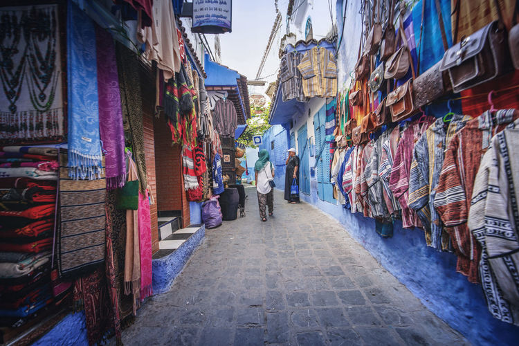 """""""The Blue City"""" - Chefchaouen, Morocco. Chefchaouen Chefchaouen Medina Medina Morocco MoroccoTrip EyeEmNewHere a new beginning Digital Nomad Travel Travel Destinations Traveling Travel Photography Photography Blue City Alley Maze Arabic Moroccans Tourism Tourist Attraction  Tourist Destination Building Exterior Architecture Street Multi Colored Built Structure Day Market The Way Forward Hanging One Person Real People Full Length Direction Retail  Walking Choice Incidental People Outdoors Retail Display"""
