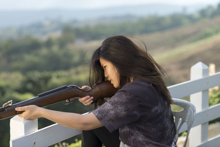 Concentrated woman aiming rifle while sitting on chair by railing over hill