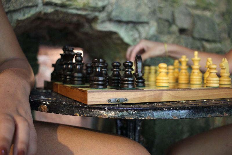 Cropped image of female friends playing chess on table