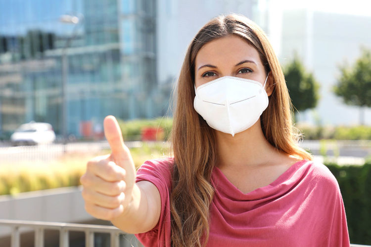 Portrait of young woman wearing flu mask holding file walking on road