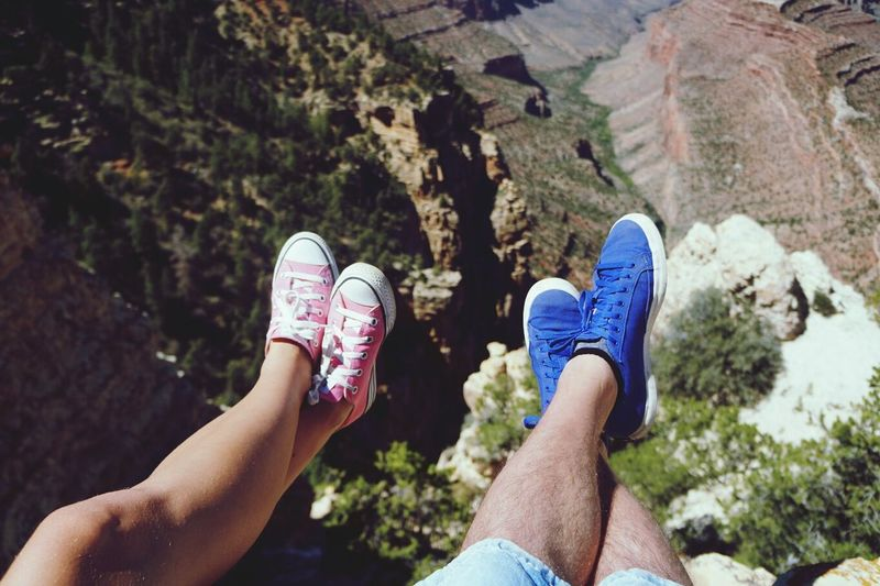 Midsection of woman and man wearing shoes over precipice