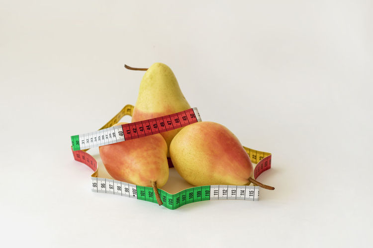 Three ripe pears and tape measure on light background, concept of a healthy lifestyle, diet, control of overweight Healthy Eating Fruit Food And Drink Food Still Life Wellbeing Freshness Close-up No People Pear Tape Measure Ripe Copy Space Dieting Healthy Lifestyle Healthy Healthy Food Bright Weight Figure Centimeter Energy Shape Fitness Calories