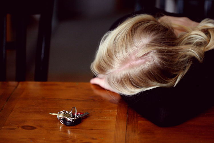 Woman leaning by keys on wooden table at home